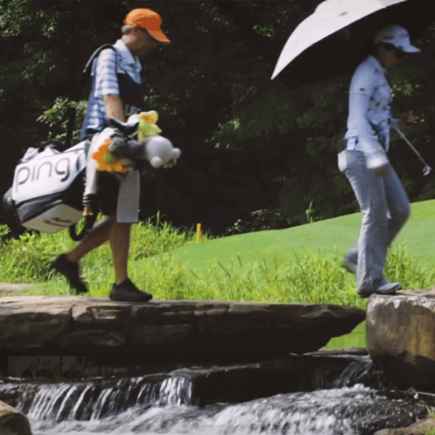 Player and caddie walking across rock waterfall